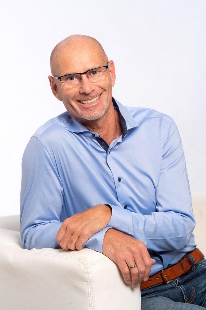 Das Foto zeigt Ralf Kohlen, lachend, von vorne, in einem Sessel