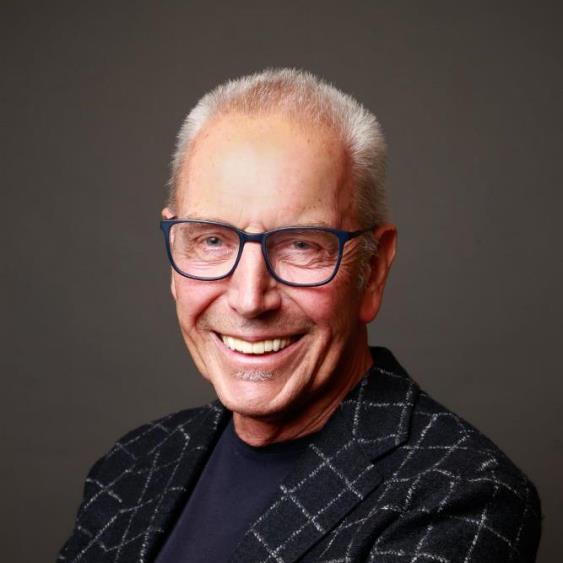 Das Foto ist ein Porträt von Rudolf A. Müller, lachend