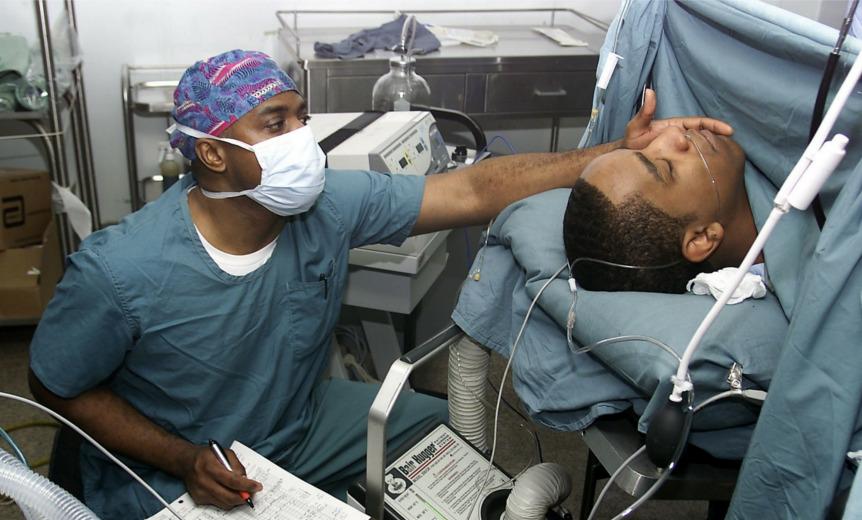 Das Bild zeigt einen Krankenpfleger, der einen wohl bewusstlosen Patienten betreut. Durch das Entwickeln von Achtsamkeit und das Reduzieren von Compliance entsteht eine hohe Qualität von Pflege.