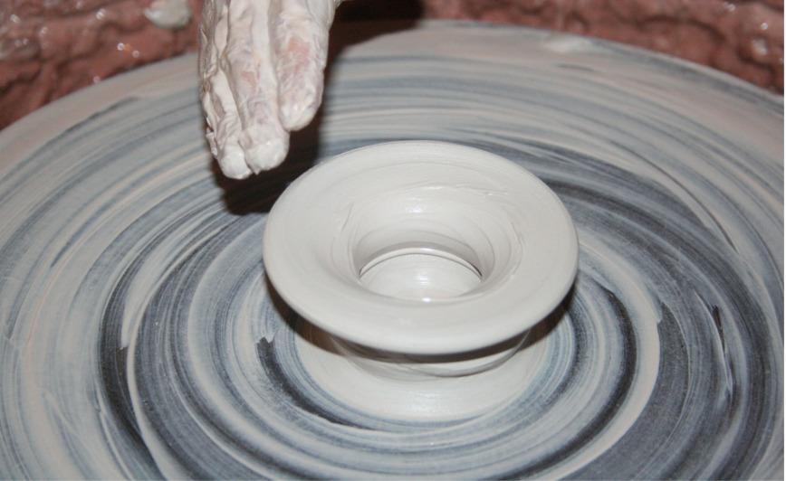 Das Foto zeigt wie ein Objekt auf einer Töpferscheibe entsteht. Für die kreative Gestaltung muss man die Kontrolle aufgeben.
