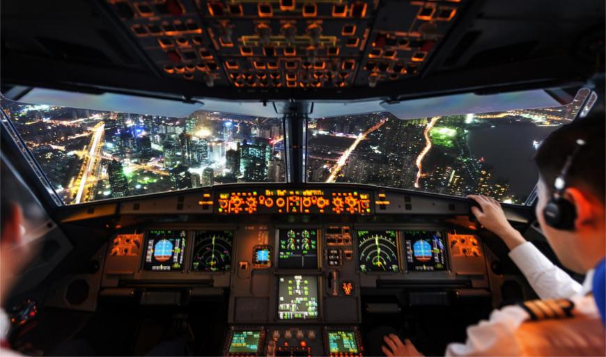 Das Foto zeigt die Innenansicht des Cockpits eines Verkehrsflugzeugs bei Nacht. Zwei Piloten steuern das Flugzeug zur Landung in einer Stadt. Jetzt getroffene Entscheidungen sollten rein kompetenzbasiert, nicht hierarchisch sein.