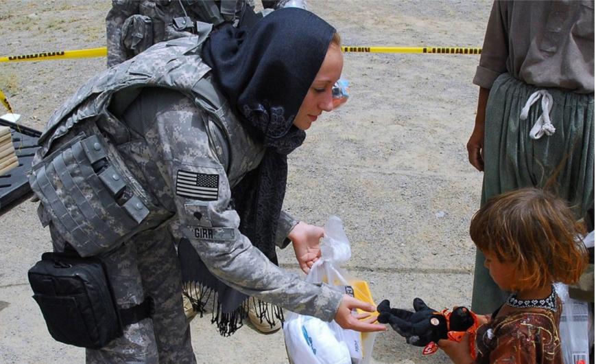Das Bild zeigt eine amerikanische Soldatin, wohl im Nahen Osten, die einem einheimischen Kind ein Spielzeug gibt. Mit dem Entwickeln von Achtsamkeit und dem Reduzieren von Compliance kann eine neue Qualität der Beziehungen entstehen.