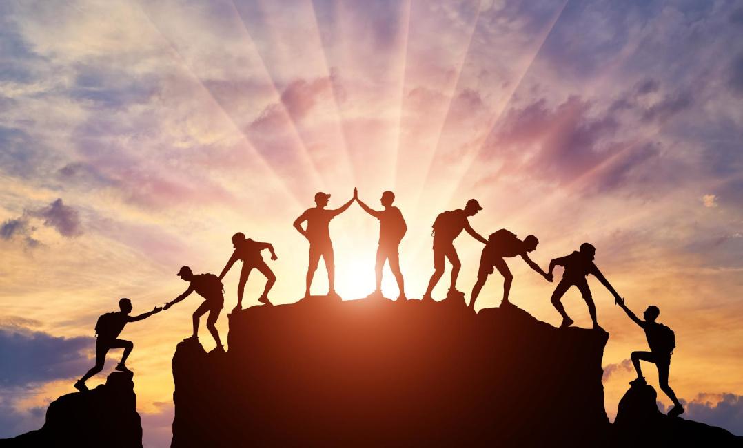 Das Bild zeigt eine Gruppe von Bergsteigern, die sich gegenseitig unterstützen, den Gipfel zu erreichen. Sinnverwirklichung statt Gewinnen-Wollen - nichts ist kraftvoller.