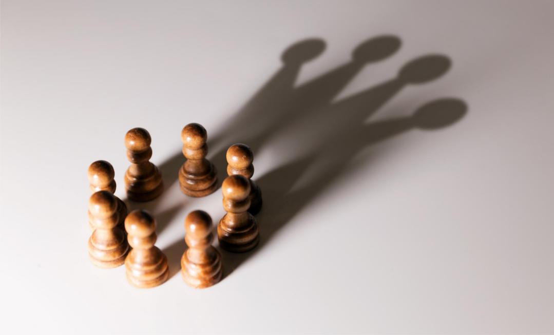 Das Bild zeigt ein Team von Bauern im Schach, die als Schattenbild eine Krone zeigen. Qualität und Agilität entstehen, wenn Kompetenz statt Hierarchie entscheidet.