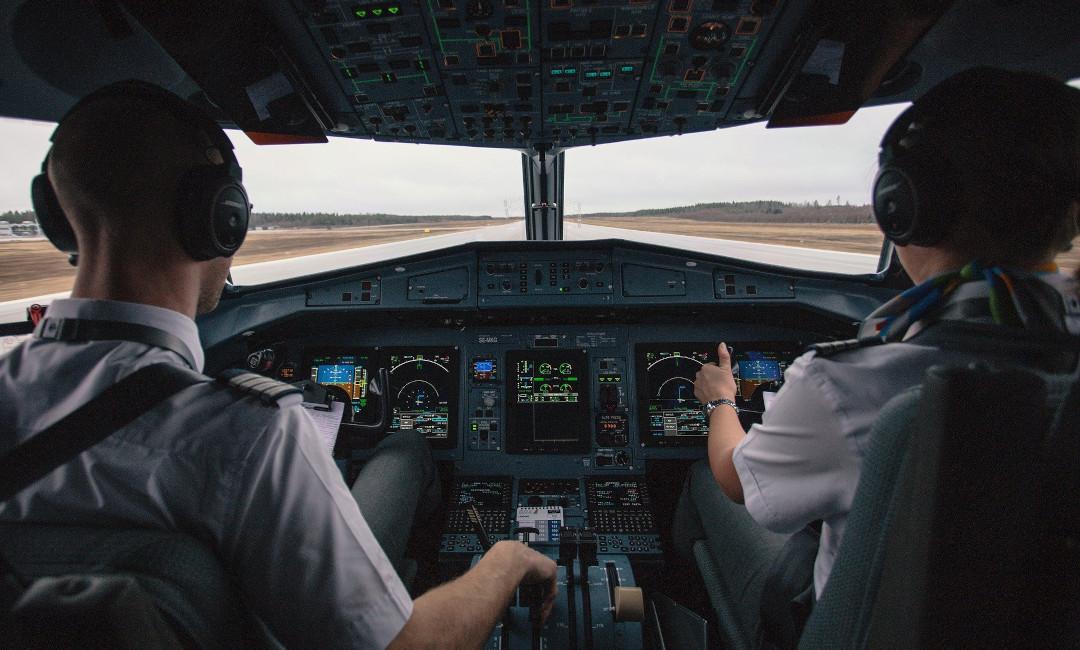 Das Foto zeigt das Cockpit eines Verkehrsflugzeugs mit zwei Piloten beim Start